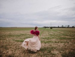 girl with red fluffy dress in field