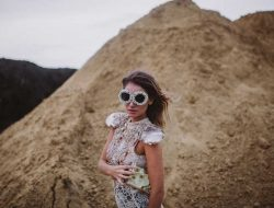 girl with sand and floral sunglasses