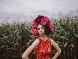 girl in corn field with coral dress and dahlia flower crown