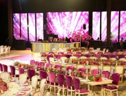 Outdoor wedding with long tables and LED screens and pink flowers from Sardinia Wedding planner
